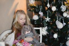 A menina perto de uma árvore de Natal com um coelho favorito do brinquedo, caixas, Natal, ano novo, estilo de vida, feriado, féri Imagem de Stock Royalty Free