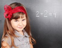 Menina perto do quadro-negro que aprende matemáticas Fotografia de Stock Royalty Free