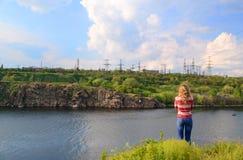 A menina perto do rio olha longe Fotografia de Stock Royalty Free
