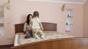 A menina perturba sua mãe para trabalhar na tabuleta vídeos de arquivo