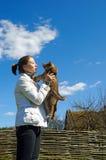 A menina pets um filhote de cachorro ao ar livre Fotos de Stock Royalty Free