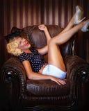 A menina Pin-acima loura no chapéu com véu senta-se em uma cadeira e ri-se Fotografia de Stock