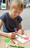 A menina pinta com uma caneta com ponta de feltro um artigo feito à mão de papel Classe do mestre do ` s das crianças no ar livre fotos de stock royalty free