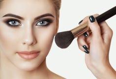 A menina pinta o pó na cara, termina os olhos do smokey prepara no salão de beleza fotos de stock