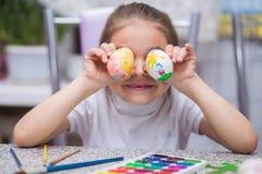 A menina pintou ovos da p?scoa com pinturas da aquarela e guarda-as perto dos olhos e dos risos entretenimento do ` s das crian?a imagem de stock royalty free