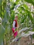 A menina pisa fora de um campo de milho e sorri imagens de stock royalty free