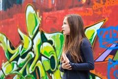 Menina por uma parede dos grafittis Foto de Stock Royalty Free