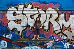 Menina por uma parede dos grafittis fotografia de stock