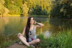 Menina positiva do moderno que olha de lado ao descansar na grama imagens de stock royalty free