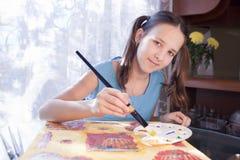 A menina positiva do schoold está pintando em casa Foto de Stock