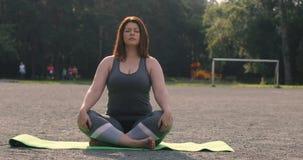 Menina positiva do tamanho que medita fora a ioga filme