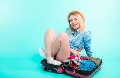 A menina positiva empacota-se na mala de viagem fotos de stock