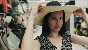 A menina positiva escolhe um acessório do verão no shopping Opinião ascendente próxima a mulher atrativa que põe sobre um chapéu  filme