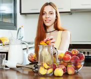 Menina positiva que cozinha bebidas dos pêssegos Fotografia de Stock