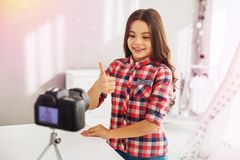 Menina pré-escolar bonito de olhos escuros de irradiação que filma seu blogue engraçado para seguidores imagem de stock