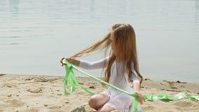 menina pré-escolar com danças uma fita ginástica em um Sandy Beach ver?o, alvorecer vídeos de arquivo