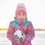 Menina pré-escolar de sorriso bonito da idade que guarda a neve Foto de Stock