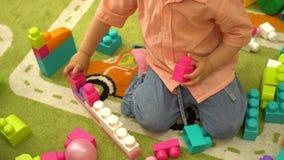 Menina pré-escolar que joga com multi blocos de apartamentos coloridos no jardim de infância Desenvolvimento infantil no infantár video estoque