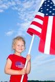 Menina pré-escolar que prende uma bandeira americana. Foto de Stock