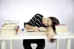A menina preguiçosa cai adormecido ao estudar Fotos de Stock