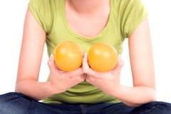 A menina prende duas laranjas em um peito. Foto de Stock Royalty Free