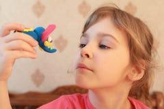 A menina prende o elefante e olha-o Imagens de Stock Royalty Free
