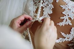 A menina prende o vestido de casamento na parte de trás da noiva Fim acima foto de stock