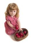 A menina prende uma cesta com maçãs vermelhas. Fotos de Stock