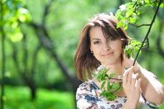 A menina prende uma filial de árvore Imagens de Stock Royalty Free