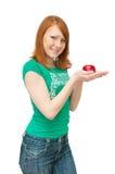 A menina prende uma maçã nas palmas Fotos de Stock
