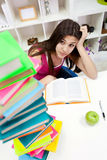 Menina preocupada do estudante que olha nos livros Foto de Stock Royalty Free