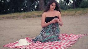 Menina preocupada que senta-se na praia e na mensagem no telefone video estoque