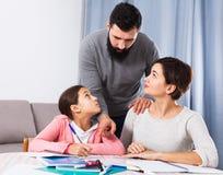 A menina prepara trabalhos de casa com pais Imagens de Stock