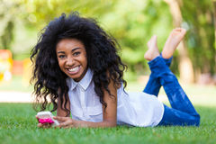 Menina preta adolescente que usa um telefone, encontrando-se na grama - p africano Fotos de Stock