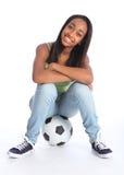 Menina preta bonita do jogador de futebol que senta-se na esfera imagem de stock royalty free