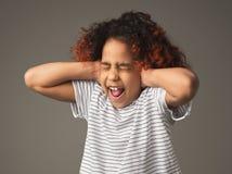 Menina preta da criança que cobre as orelhas com as mãos imagem de stock