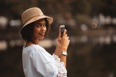 A menina preta está tomando fotos da lagoa através do smartphone fotos de stock royalty free