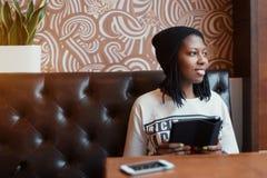 Menina preta nova de sorriso que senta-se no sofá de couro no café Fotografia de Stock