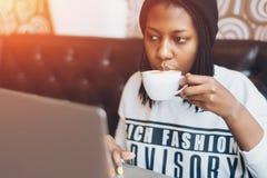 Menina preta nova no café bebendo do café e trabalho no portátil Foto de Stock