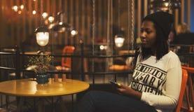 Menina preta nova no café que guarda um smartphone Imagens de Stock Royalty Free