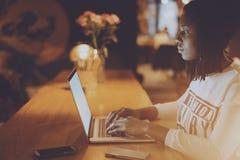 Menina preta nova no café que trabalha no portátil Imagens de Stock