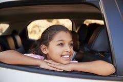 Menina preta nova que olha fora da janela de carro que sorri, vista dianteira imagens de stock royalty free
