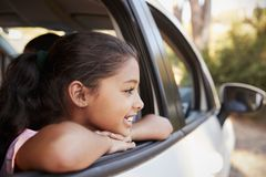 Menina preta nova que olha fora da janela de carro que sorri, vista lateral imagens de stock royalty free