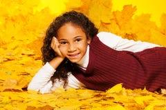 A menina preta pequena coloca nas folhas de bordo do outono Fotos de Stock