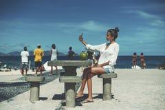 Menina preta que toma o selfie perto da área da praia com povos ao redor imagens de stock royalty free
