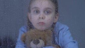 Menina preteen abandonada que abraça o urso de peluche e que olha na janela no dia chuvoso filme