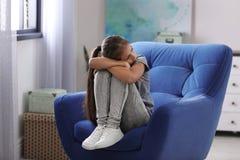Menina preteen deprimida que senta-se na poltrona fotos de stock