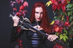 A menina principal vermelha bonita alta que veste o equipamento de couro preto que guarda uma espada da fantasia pela lâmina cerc fotografia de stock