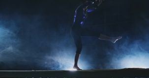 A menina profissional da ginasta executa um salto com uma rotação no feixe de equilíbrio no movimento lento Fume a cor azul no gy filme
