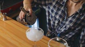 A menina profissional fêmea do barman que faz o vidro de derramamento do abanador do suco do álcool do cocktail granulou o close  vídeos de arquivo